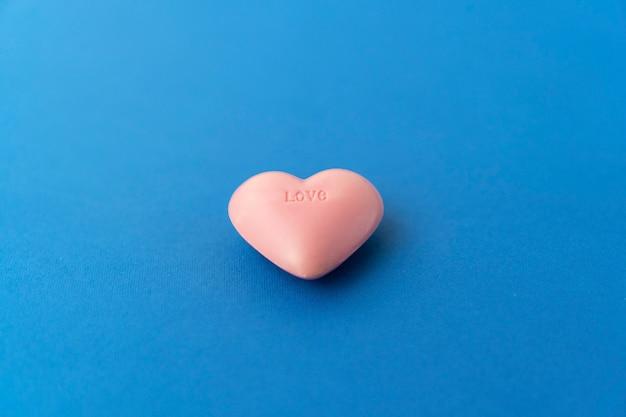 Composizione vista dall'alto del cuore rosa su sfondo colorato. concetto di relazione romantica.