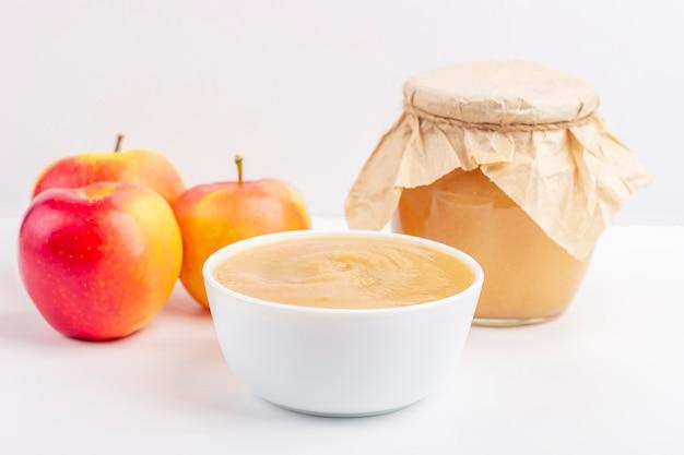 Composta di mele fatta in casa fresca in ciotola e barattolo bianchi con purea di frutta sulla tavola bianca. il concetto di corretta alimentazione e alimentazione sana. alimenti biologici e vegetariani cibo per neonato
