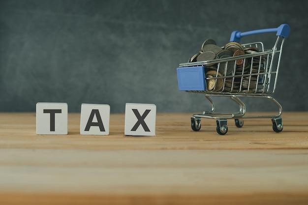 Comprando e facendo compere il concetto di imposta in linea, tassa su di legno con i soldi pieni conia in carrello sulla tavola di legno