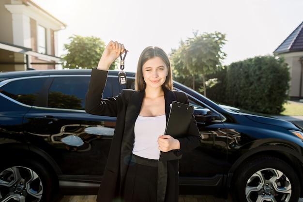 Comprare o vendere un'auto. giovane donna graziosa che tiene le chiavi che stanno davanti al nuovo incrocio nero dell'automobile all'aperto.