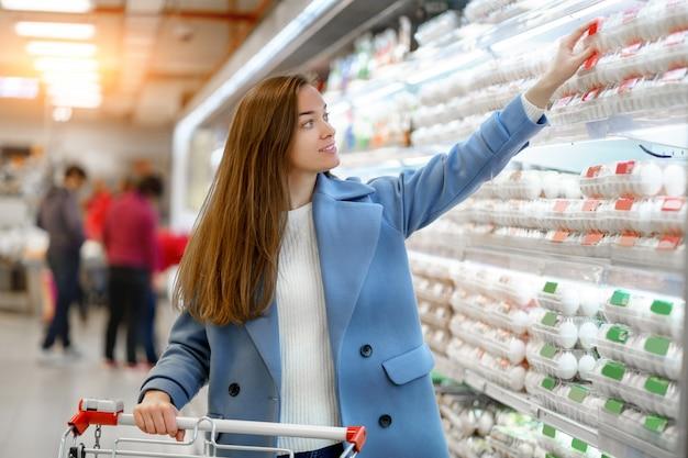 Compratore della donna con il carrello nel negozio di alimentari durante la scelta e l'acquisto di uova di gallina fresche mentre lo shopping di cibo