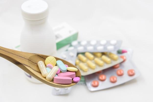 Compressa colorata in cucchiaio di legno e pillole bianche medicina e bottiglia su sfondo bianco