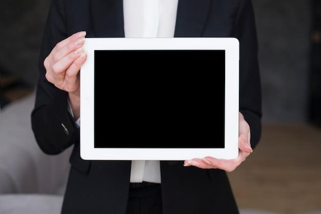 Compressa della tenuta della donna di affari con lo schermo in bianco