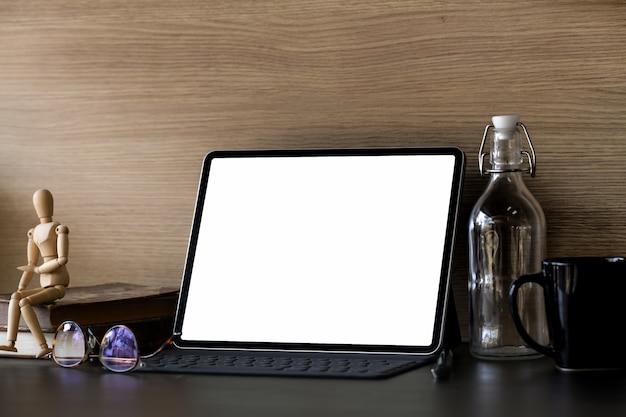 Compressa dello schermo in bianco dell'area di lavoro con i rifornimenti per ufficio