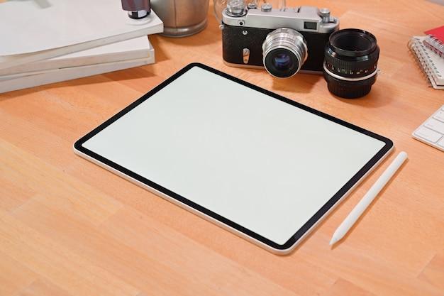 Compressa dello schermo in bianco sullo scrittorio alla moda di legno con i rifornimenti creativi del fotografo e lo spazio della copia
