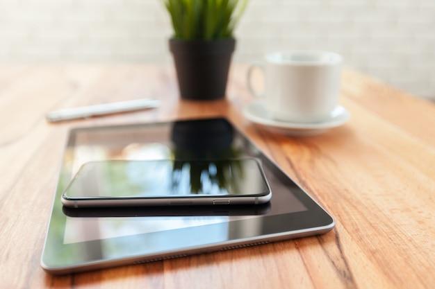 Compressa e smart phone di digital sulla tavola di legno