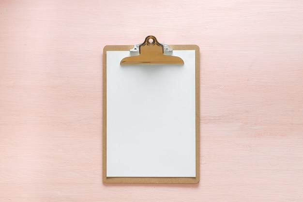Compressa in bianco della cartella isolata sullo spazio rosa della copia. posa piatta minimalista femminile per blogger, designer, siti