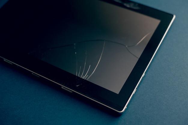 Compressa moderna su un fondo blu classico con le crepe. schermo rotto di un tablet, smartphone o laptop. concetto di riparazione. copyspace