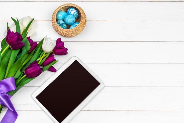 Compressa, tulipani variopinti ed uova di pasqua su superficie di legno
