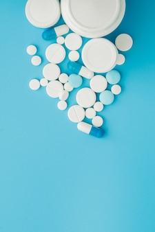 Compresse assortite delle pillole della medicina farmaceutica e capsule e bottiglia su fondo blu