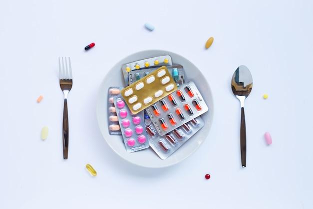 Compresse, capsule e pillole variopinte con il piatto, la gente e il cucchiaio bianchi su bianco
