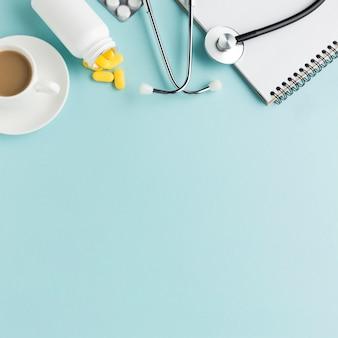 Compresse che cadono dalla bottiglia con una tazza di caffè; compresse confezionate in blister; stetoscopio; blocco note a spirale su sfondo blu