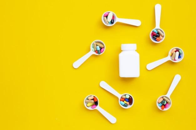 Compresse colorate con capsule e pillole su sfondo giallo.