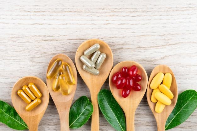 Compresse di pillole, capsule e integratori biologici vitaminici in cucchiai di legno