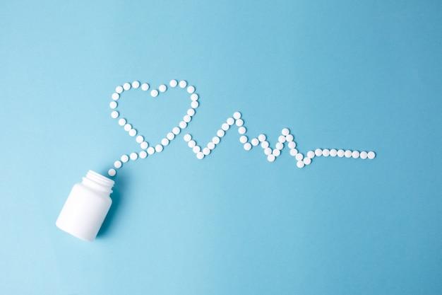 Compresse medicinali sotto forma di cuore e cardiogramma, capsule su sfondo blu. il concetto di un cuore sano,