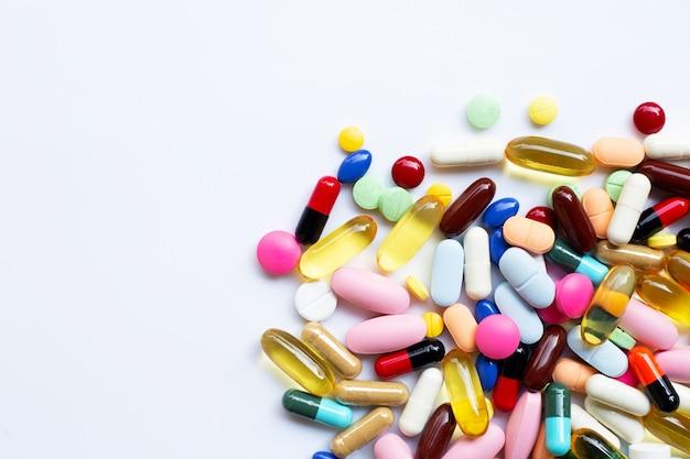 Compresse variopinte con le capsule e le pillole su bianco.