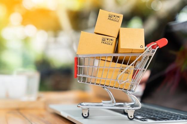 Compri le scatole di pacchetto di concetto online in carretto e sul computer portatile sulla tavola con lo spazio della copia