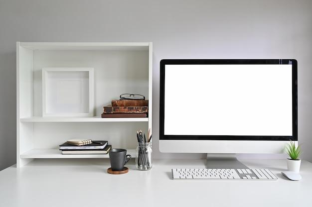 Computer del mockup dell'area di lavoro sulla scrivania e libri, cornice per foto e libri sugli scaffali.