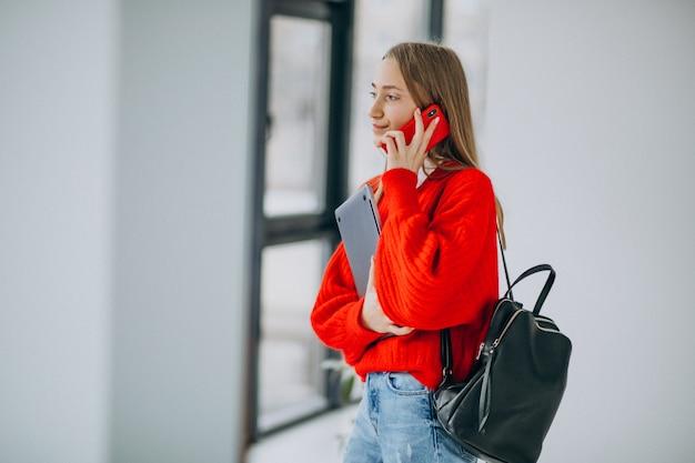 Computer della tenuta della studentessa e parlare al telefono dalla finestra