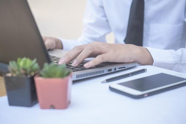 Computer di battitura a macchina dell'uomo d'affari che lavora nell'ufficio