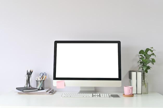Computer e forniture per ufficio dell'area di lavoro sul posto di lavoro dell'ufficio con esposizione vuota del computer del pc del modello.