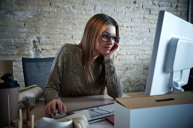 Computer funzionante della donna di affari all'ufficio