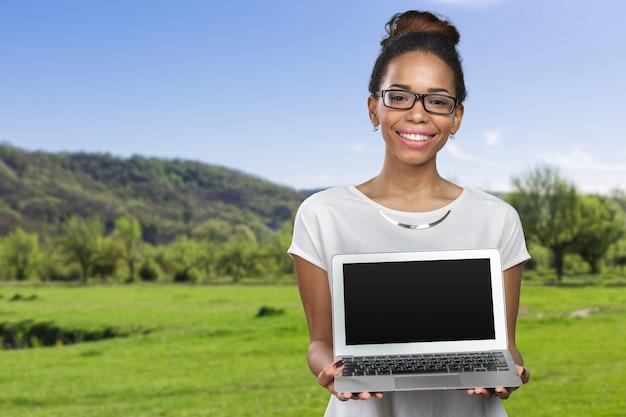 Computer portatile afroamericano della tenuta della donna