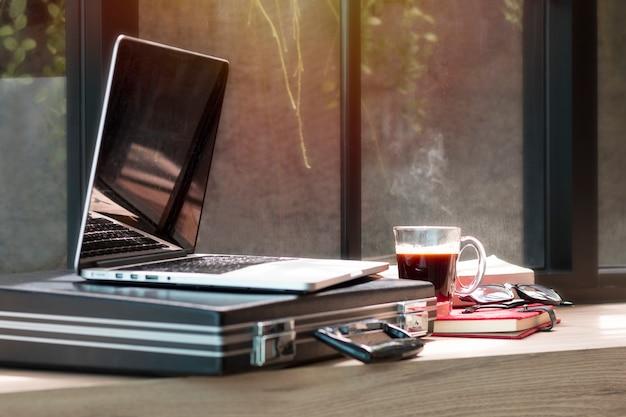 Computer portatile aperto, borsa documenti, occhiali e libro al bar.