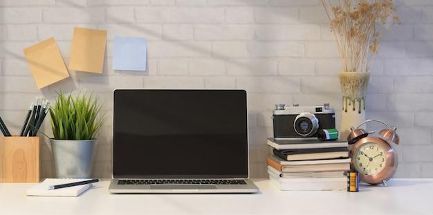 Computer portatile aperto con forniture per ufficio