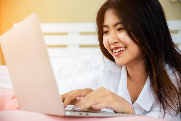Computer portatile asiatico asiatico di uso della donna sul letto