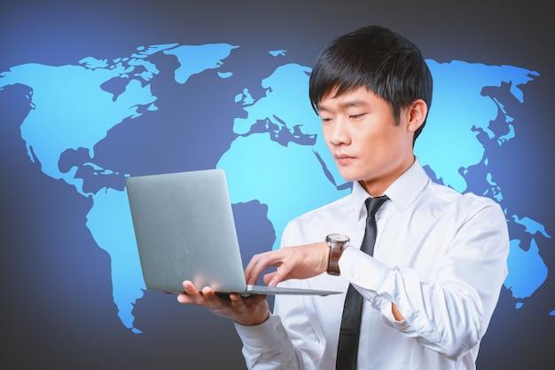 Computer portatile asiatico sorridente della tenuta dell'uomo d'affari dei giovani