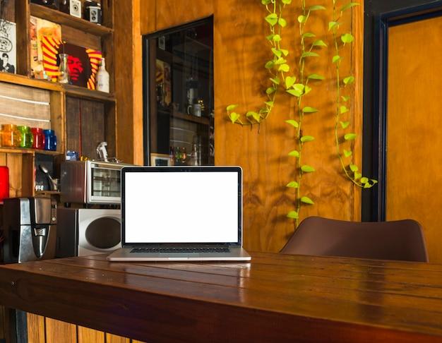Computer portatile bianco dello schermo in bianco sul tavolo da pranzo a casa