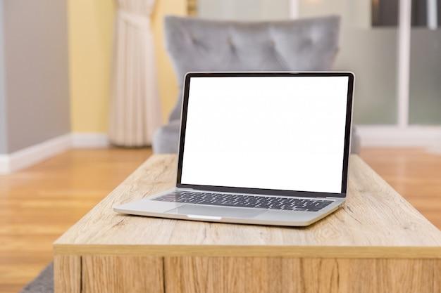 Computer portatile che mostra schermo in bianco sulla vista frontale del tavolo da lavoro nella casa