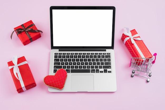 Computer portatile con cuore fatto a mano in mezzo a regali e carrello