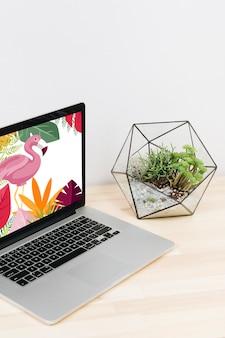 Computer portatile con fenicottero sullo schermo sulla tavola di legno