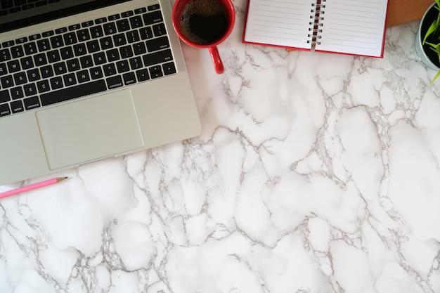 Computer portatile con forniture per ufficio sul desktop di marmo