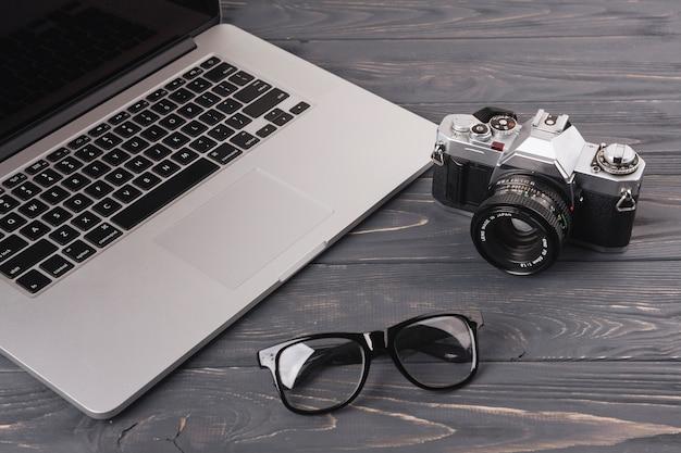 Computer portatile con fotocamera e bicchieri sul tavolo