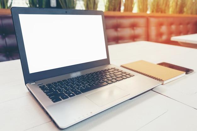 Computer portatile con il taccuino dello schermo bianco in bianco e lo smart phone sul tavolo nella stanza dell'ufficio; taccuino nella caffetteria.