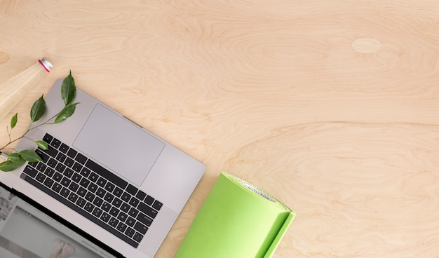 Computer portatile con la stuoia di yoga sulla vista superiore del pavimento di legno