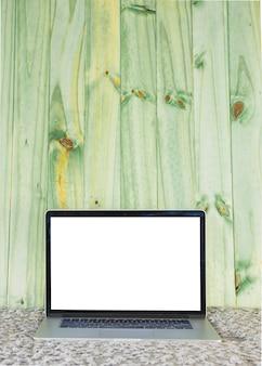 Computer portatile con lo schermo bianco in bianco sul sofà contro la plancia di legno verde