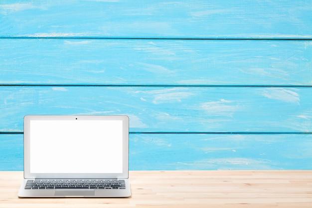 Computer portatile con lo schermo bianco in bianco sulla tavola di legno leggera contro la parete o la superficie di legno blu.