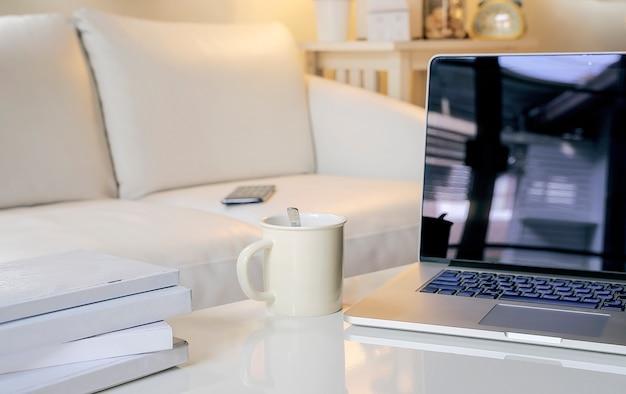 Computer portatile con lo schermo in bianco sul tavolino da salotto bianco con lo spazio della copia.