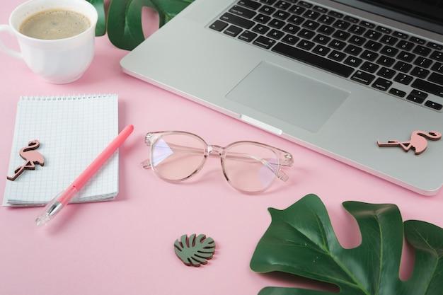 Computer portatile con notebook e piccoli fenicotteri sul tavolo rosa