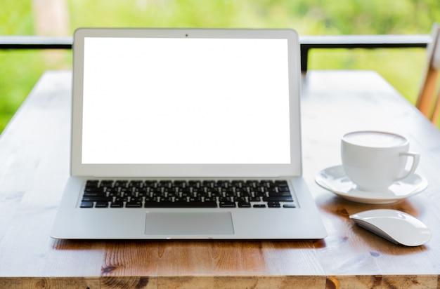 Computer portatile con schermo in bianco su un tavolo di legno e una tazza di caffè