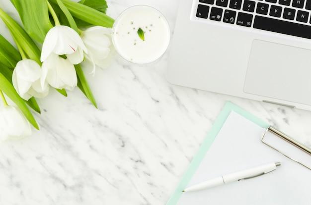 Computer portatile con tulipani e appunti sul tavolo luminoso