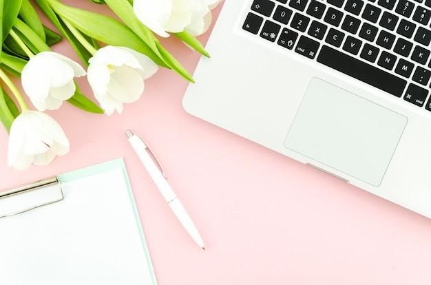 Computer portatile con tulipani e appunti sul tavolo