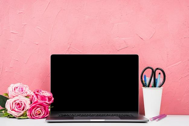 Computer portatile con vista frontale con bouquet di rose