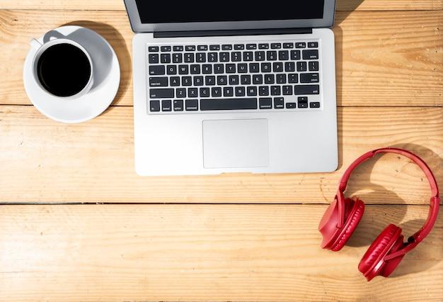 Computer portatile, cuffie e tazza di caffè sulla tavola di legno