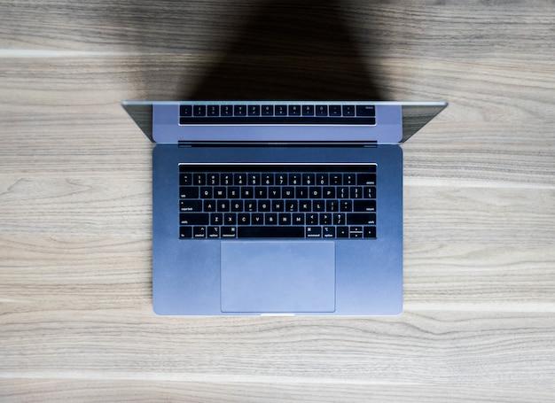 Computer portatile d'argento sulla tavola di legno