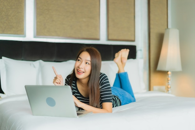 Computer portatile del computer di uso della bella giovane donna asiatica del ritratto sul letto nell'interno della camera da letto